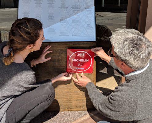 Carla Carreras i Pere Miquel Carreras penjant la placa que indica que Les Corones és un establiment recomanat a la Guia Michelin 2018.